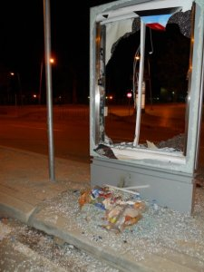 A smashed glass billboard holder lays testament to the frenzied riot outside the airport.